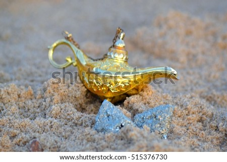 genie lamp with fools gold on the beach