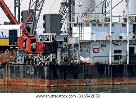 GENOA, ITALY - AUGUST 2, 2011: A working platform in the port of Genoa. Workers involved with the dredging of the seabed and the implementation of the foundations of the new quay.