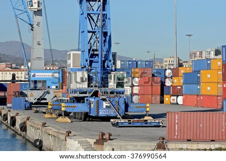 GENOA, ITALY - FEBRUARY 5, 2016: Containers on the docks of the commercial port of Genoa. In the picture, containers with cranes on the quay.