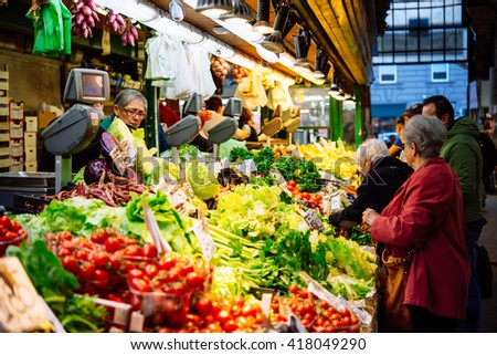 GENOA, ITALY - OCTOBER 23, 2015: People buy different fruits and vegetables at the local market in Genoa, Italy.