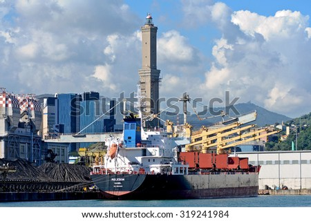 GENOA, ITALY - SEPTEMBER 21, 2015: Import of coal. The cargo ship MOLESON under the lighthouse symbol of the city of Genoa.