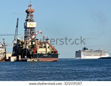 GENOA, ITALY - SEPTEMBER 24, 2015: The Saipem 10000, an oil drilling ship of Saipem, a subsidiary of Eni. In the background a passenger ship of the MSC.