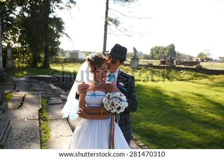 gentele groom hugs his wife - stock photo