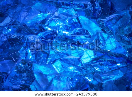 Gentle azure backdrop of shiny, water-washed crystal stones with jagged edges, mysteriously lit ultramarine glow. Close up view with space for text