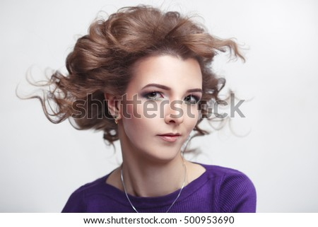 Gentle beauty portrait of a young girl with Nude make-up and developing the wind in on a light gray background.