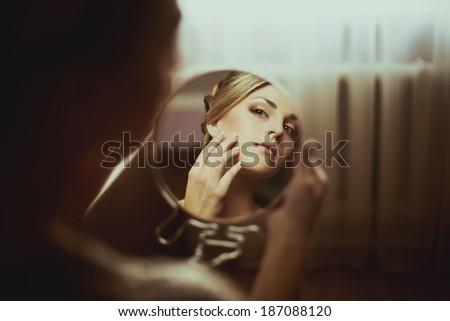 gentle bride looks in the mirror  - stock photo