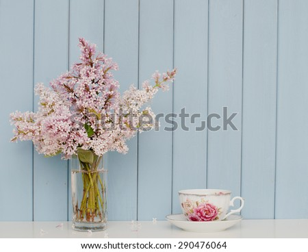 Gentle bunch of lilac and china teacup on the table on blue wooden background - stock photo