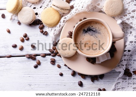 Gentle colorful macaroons and  coffee in mug on color wooden  background - stock photo