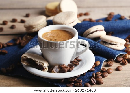 Gentle colorful macaroons and  coffee in mug on wooden table background - stock photo