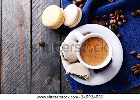 Gentle colorful macaroons and  coffee in mug on wooden table background, top view - stock photo