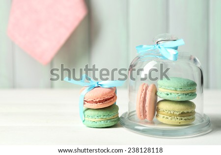 Gentle colorful macaroons in glass bell jar on color wooden table background - stock photo