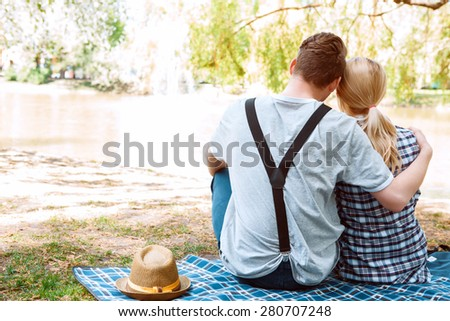 Gentle embrace. Back view of couple of young people sitting on blue cover and embracing on background of park with lake. - stock photo