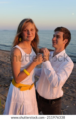 Gentle embrace of a young couple in love outside in summer on the lake