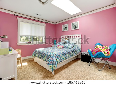 Gentle girls bedroom with white bed and pink walls. View of bed with blue bedding,blue chair