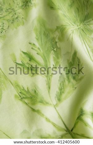 Gentle hand painted silk with green leaf print. Handmade batik. Shallow focus - stock photo