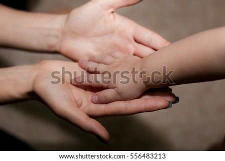gentle hands mother holding a tiny baby hand