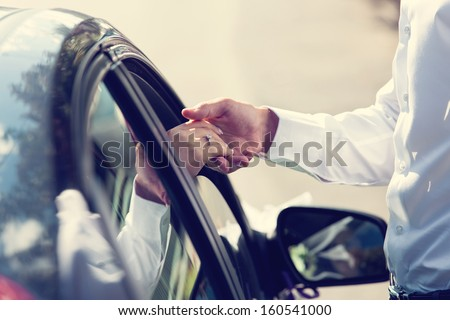 Gentle holding hands near car with wedding couple with ring - stock photo