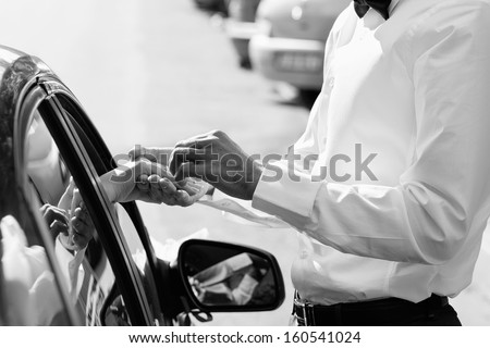 Gentle holding hands near car with wedding couple with ring black and white