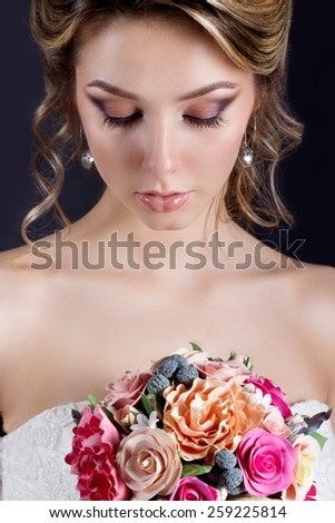 gentle portrait of happy smiling beautiful sexy girls in white wedding dress with a wedding bouquet in hand with beautiful hair and bright make-up, photography Studio - stock photo