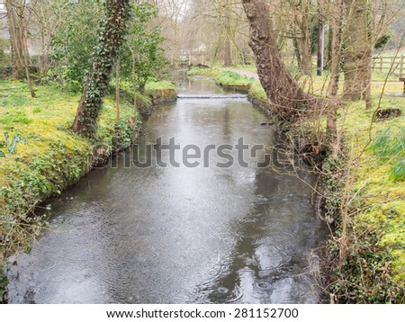 Gentle rain falling on a small stream makes patterns on the water - stock photo