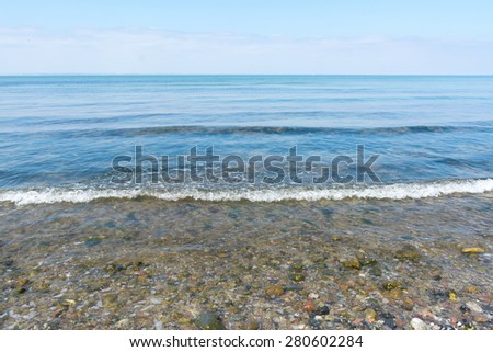 gentle sea surf on a beach of pebbles on the shore of the Baltic Sea, horizon and blue sky, frontal
