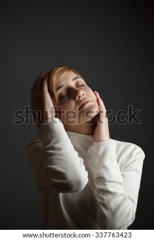 Gentle, sweet girl on a black background with closed eyes
