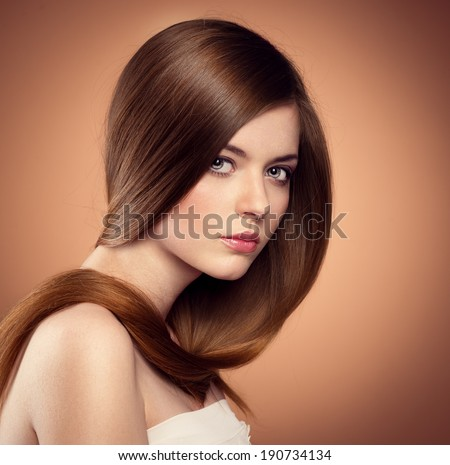 Gentle teenage girl showing her healthy long straight hair. Beautiful Caucasian female model with perfect glossy hair posing in studio.  - stock photo