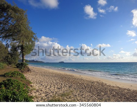 Gentle wave lap on Waimanalo Beach looking towards Mokulua islands with path along the shore on a nice day Oahu, Hawaii. - stock photo