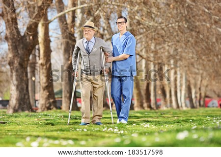 Gentleman and a male nurse walking in park on a sunny day - stock photo