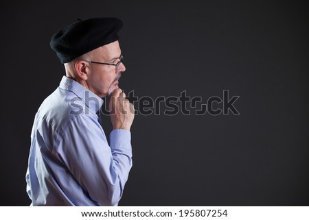 gentleman in shirt and beret and glasses thinking