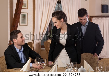 Gentleman moving a way chair of attractive woman