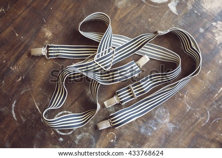 Gentleman's suspenders on a on a vintage wooden board  - stock photo