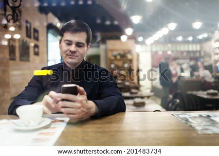 Gentleman sitting at the table using his phone texting and drinking coffee - stock photo