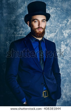 Gentleman with beard and mustache wearing elegant suit and top hat. Old style fashion.  - stock photo