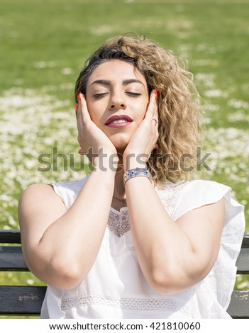 Gently Rubbing My Temples. A young woman sitting in the sun is gently massaging her temples with her eyes shut as she enjoys one of the first warm days of the year.