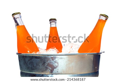 Genuine Glass Bottles of Orange Soda in a Steel Ice Bucket filled with ice. Isolated on white with room for your text. Orange Soda is enjoyed by thirsty people around the world. A refreshing drink