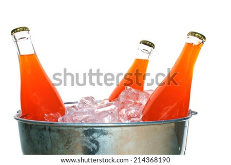 Genuine Glass Bottles of Orange Soda in a Steel Ice Bucket filled with ice. Isolated on white with room for your text. Orange Soda is enjoyed by thirsty people around the world. A refreshing drink - stock photo