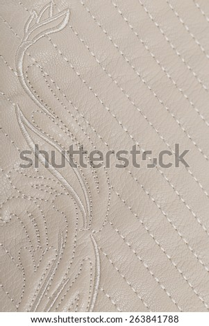 Genuine leather. Cream with embroidered flower. - stock photo