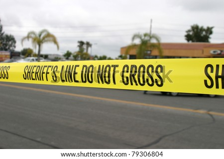 """Genuine """"Sheriff's Line Do Not Cross"""" caution tape collected from the scene of a murder. - stock photo"""