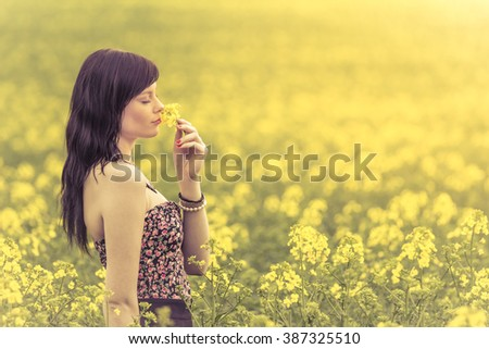 Genuine woman in meadow of yellow flowers sniffing flower. Attractive beautiful young girl enjoying the warm summer sun in a wide green and yellow meadow. Part of series. - stock photo