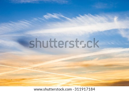 Geo engineering through airplane chemtrails sprayed in the sky, making it cloudy and polluting the environment.   - stock photo
