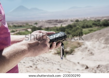 """Geocacher in the desert of """" Atacama """", Chile, seeks for a cache.  - stock photo"""