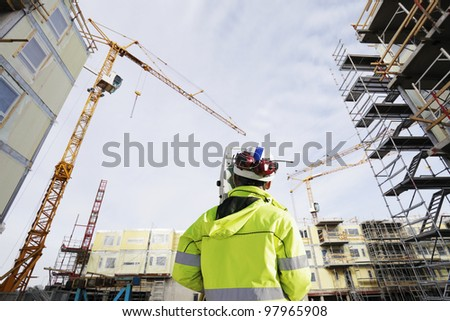 geodetist with measuring instrument inside large building site - stock photo