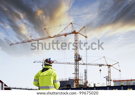 geodetist with measuring instruments, building-site in background, sunset shot - stock photo