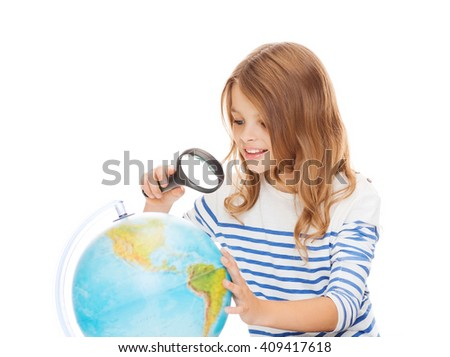 geography, education, people, children and school concept - little student girl looking at globe with magnifier - stock photo
