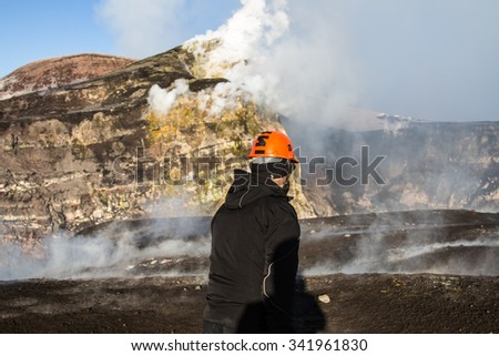 geologist looks at the craters of the erupting volcano Etna - stock photo