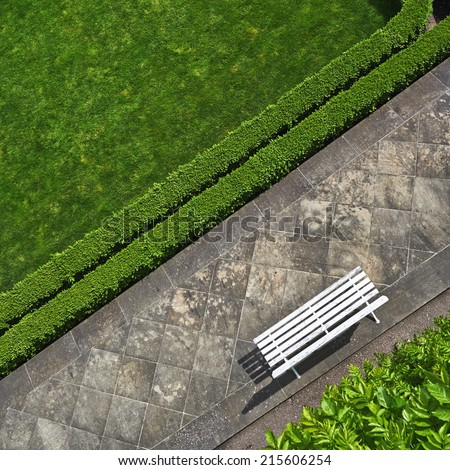 Geometric background with a white bench in a green park. Top view - stock photo
