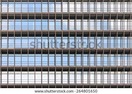 Geometrically correct architectural background of modern office building facade with blue sky and clouds reflection in windows - stock photo