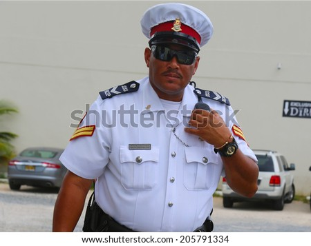 GEORGE TOWN, GRAND CAYMAN - JUNE 12: Senior constable from Royal Cayman Islands Police Service in George Town on June 12, 2014.  - stock photo