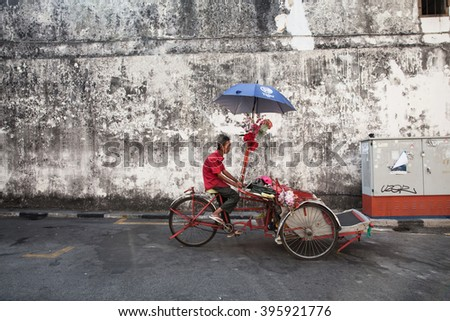 George Town,  Malaysia - March 21, 2016: Cycle rickshaw is riding down the street on March 21, 2016 in George Town, Penang, Malaysia.
